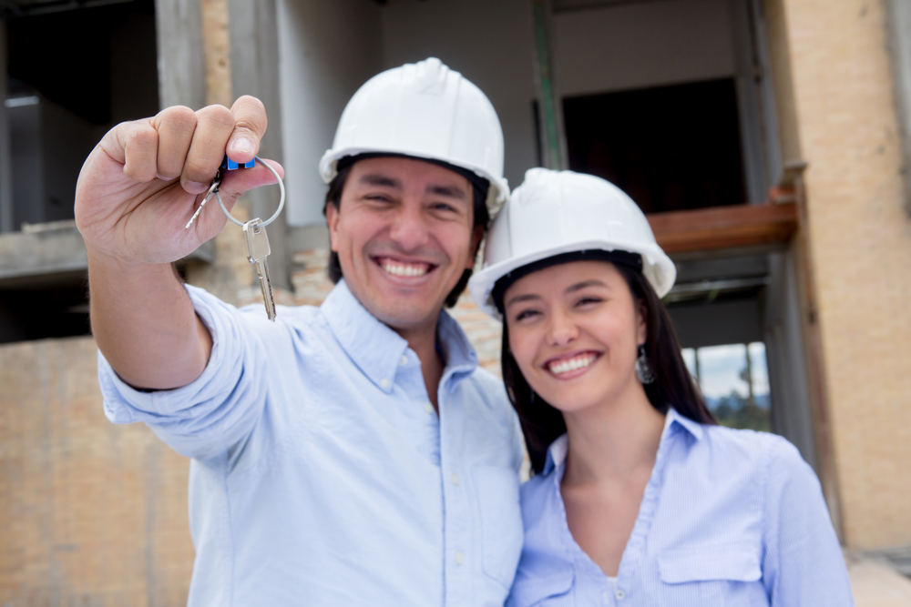 Couple at a construction site holding keys to their new house