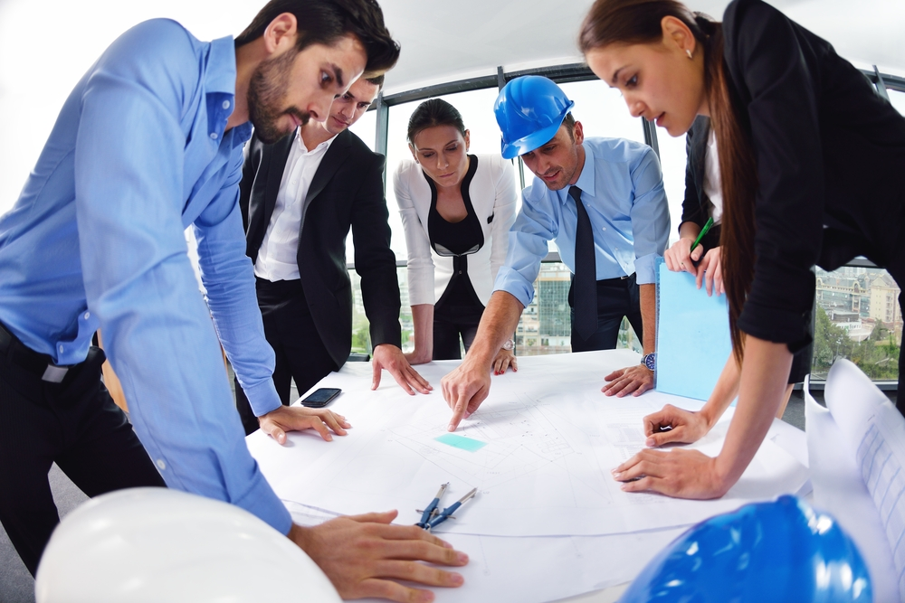 business people group on meeting and presentation  in bright modern office with construction engineer architect and worker looking building model and blueprint planbleprint plans-1